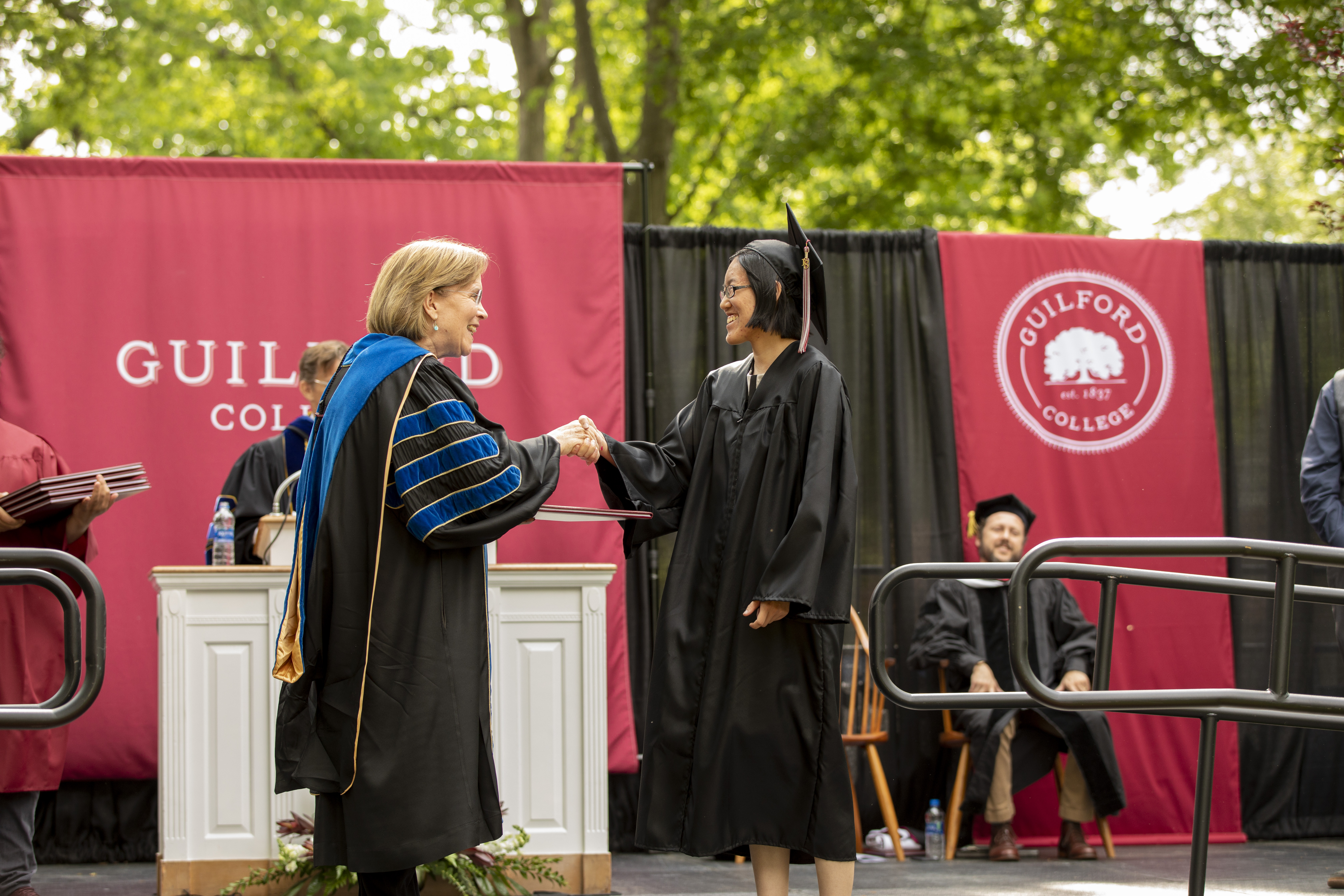 President Jane K. Fernandes (left) hands a student a diploma at Commencement.