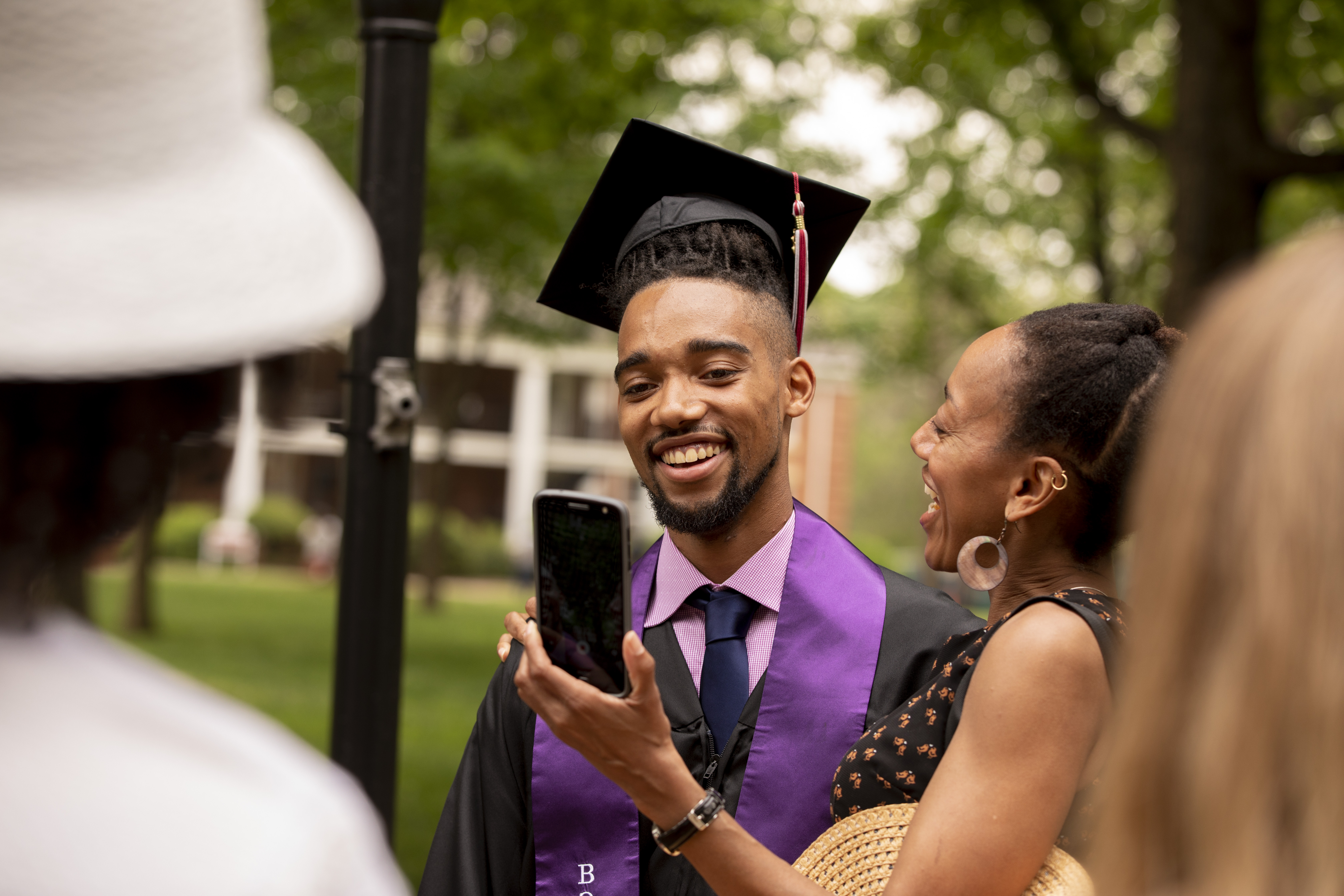 A friend shows a student a phone photo after Commencement.