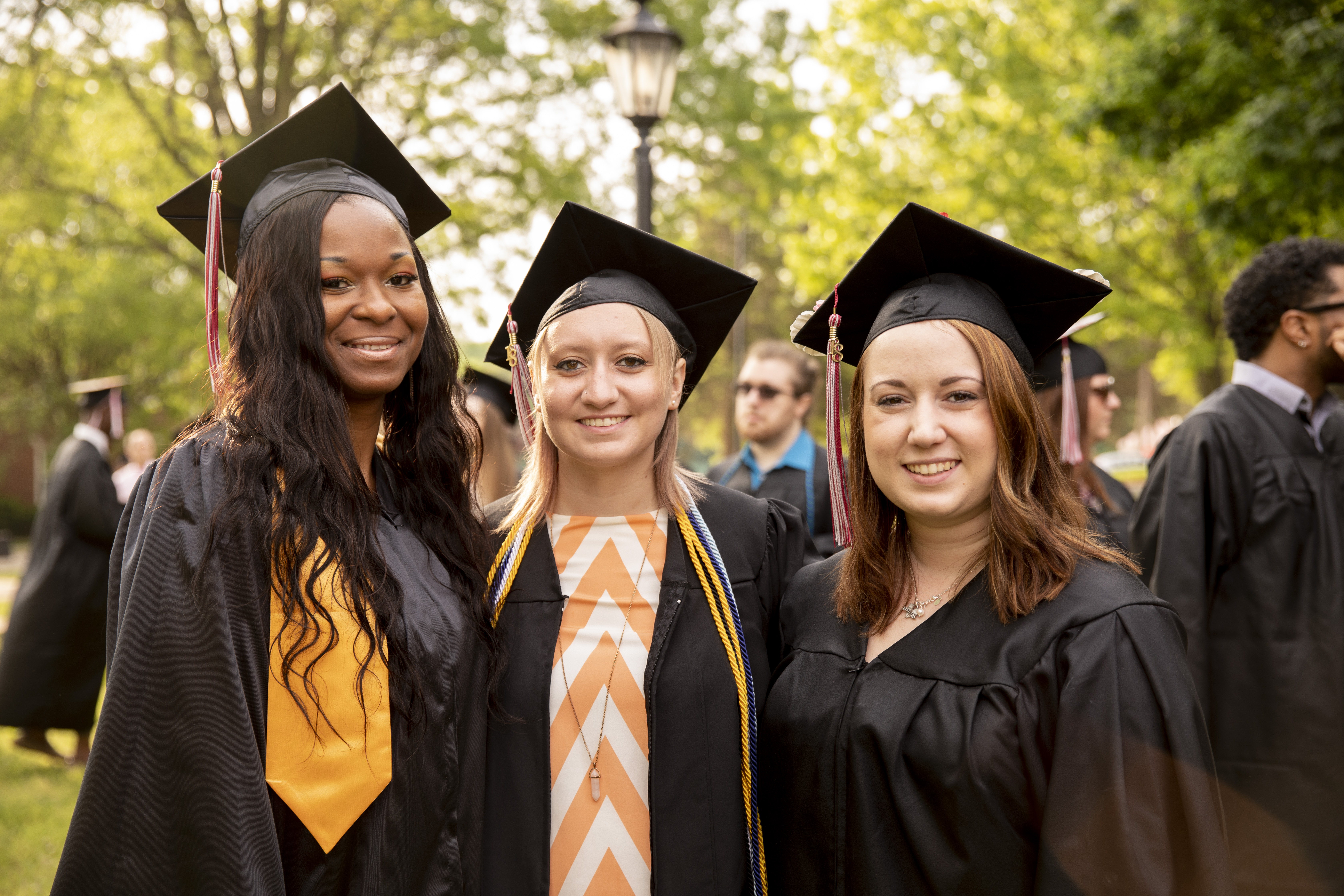 Three students take a photo together after Commencement.