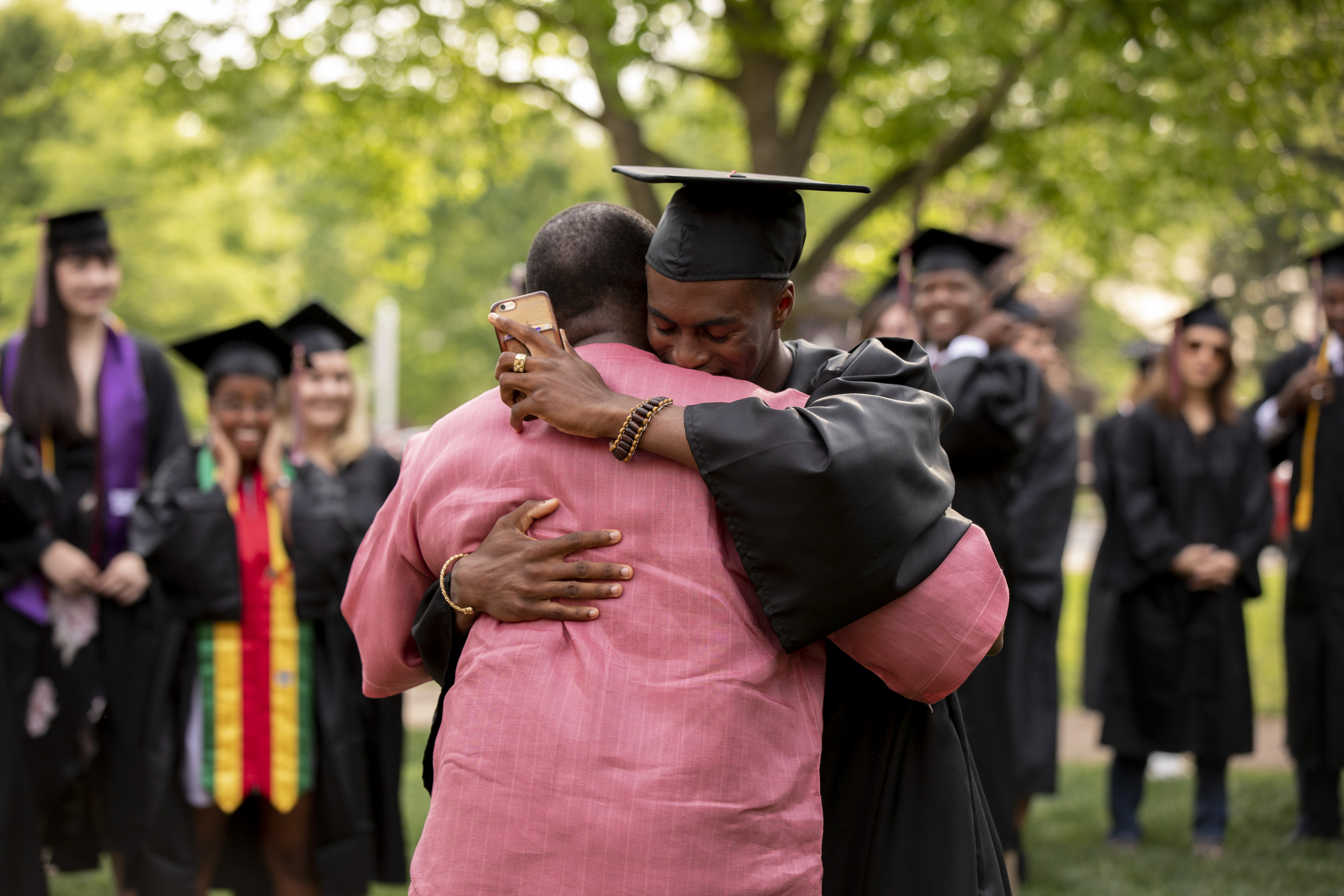 A student hugs a friend after Commencement.