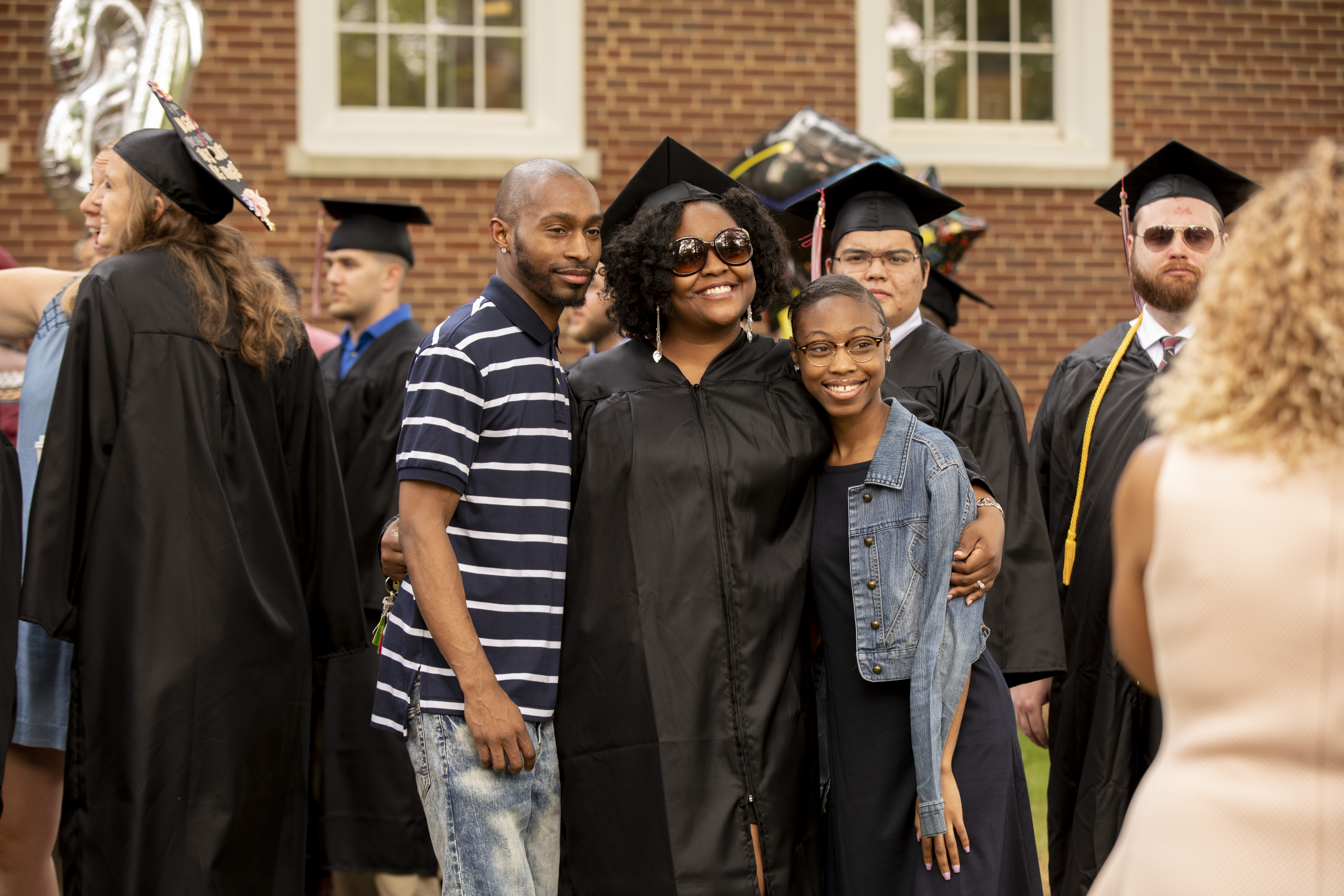 A family takes a photo after Commencement.