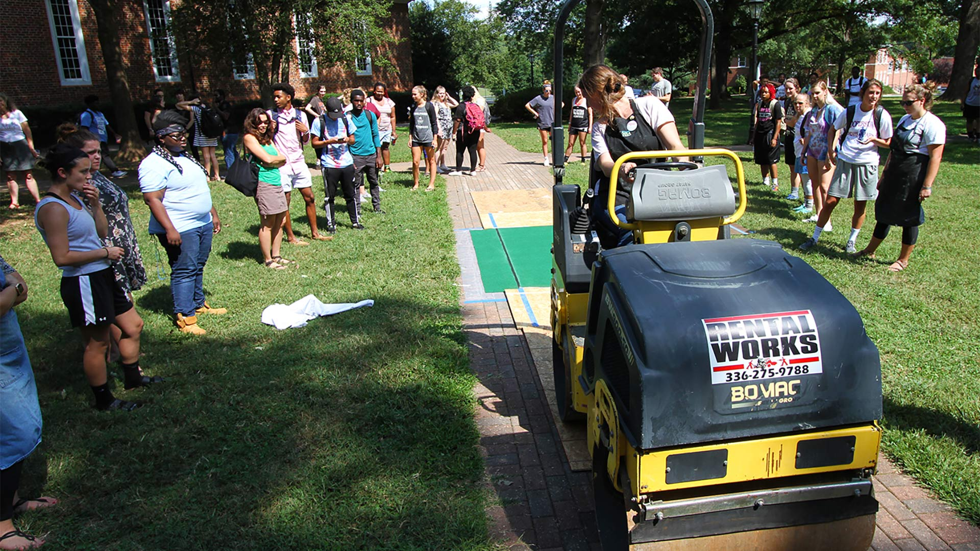 That ought to do it! Students use a steam roller to create art prints during Arts on the Quad.