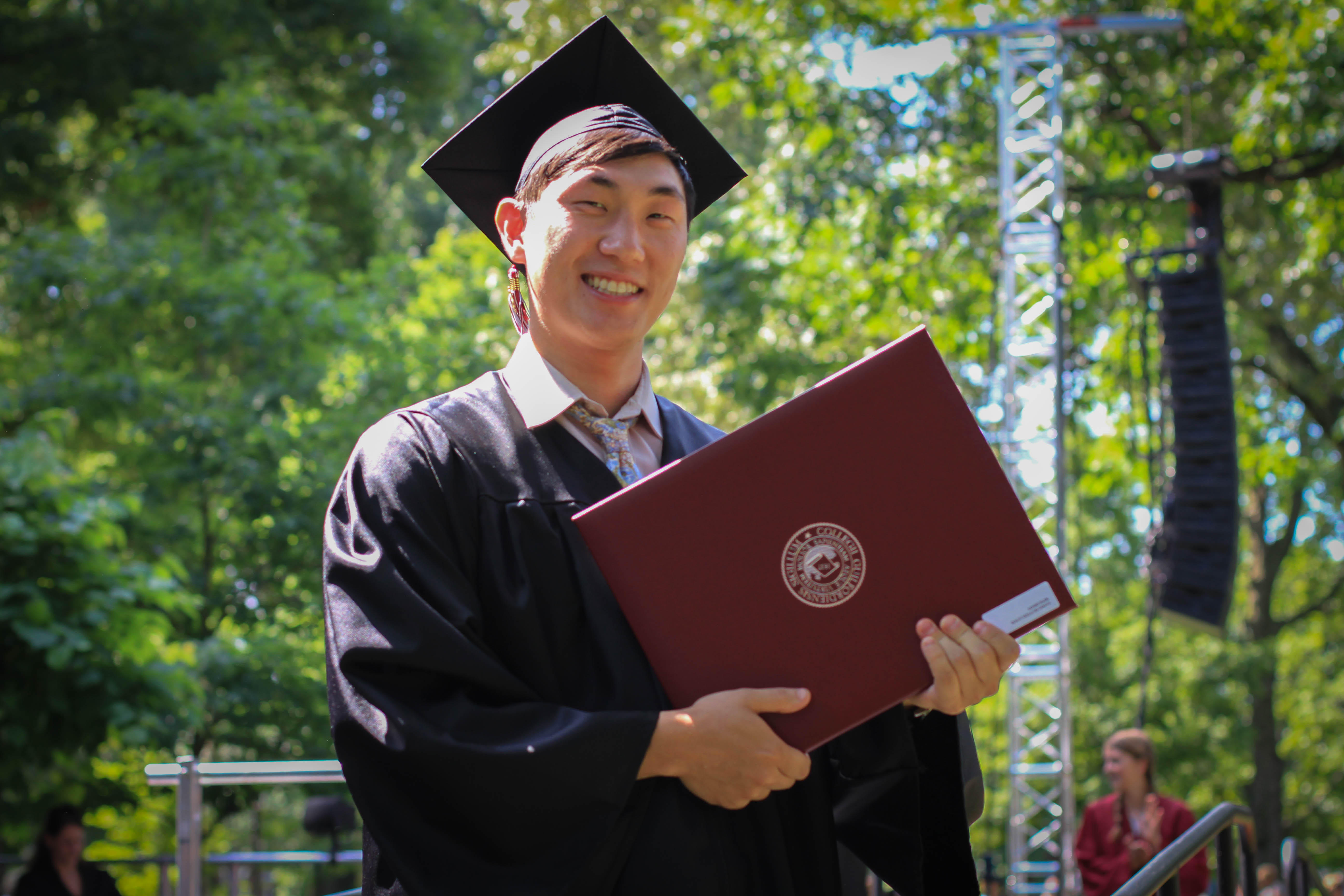 A graduate poses with his diploma.
