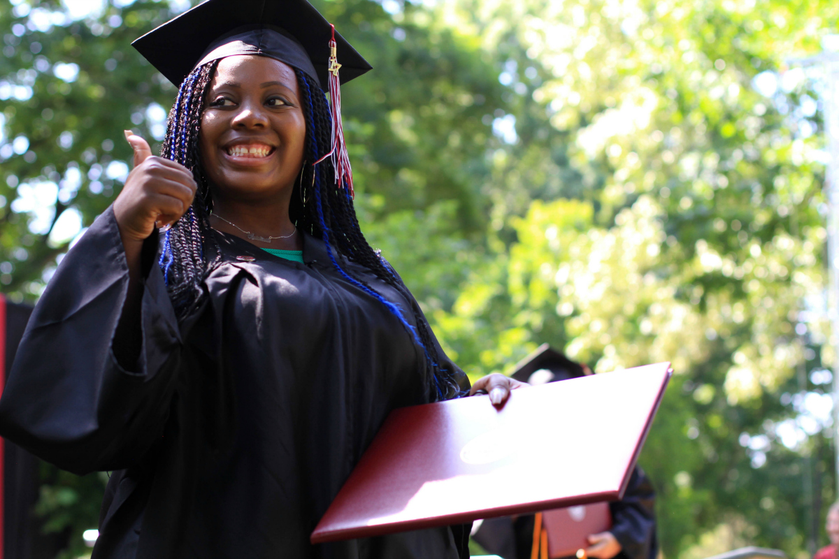A student flashes a thumbs-up sign after accepting her diploma.
