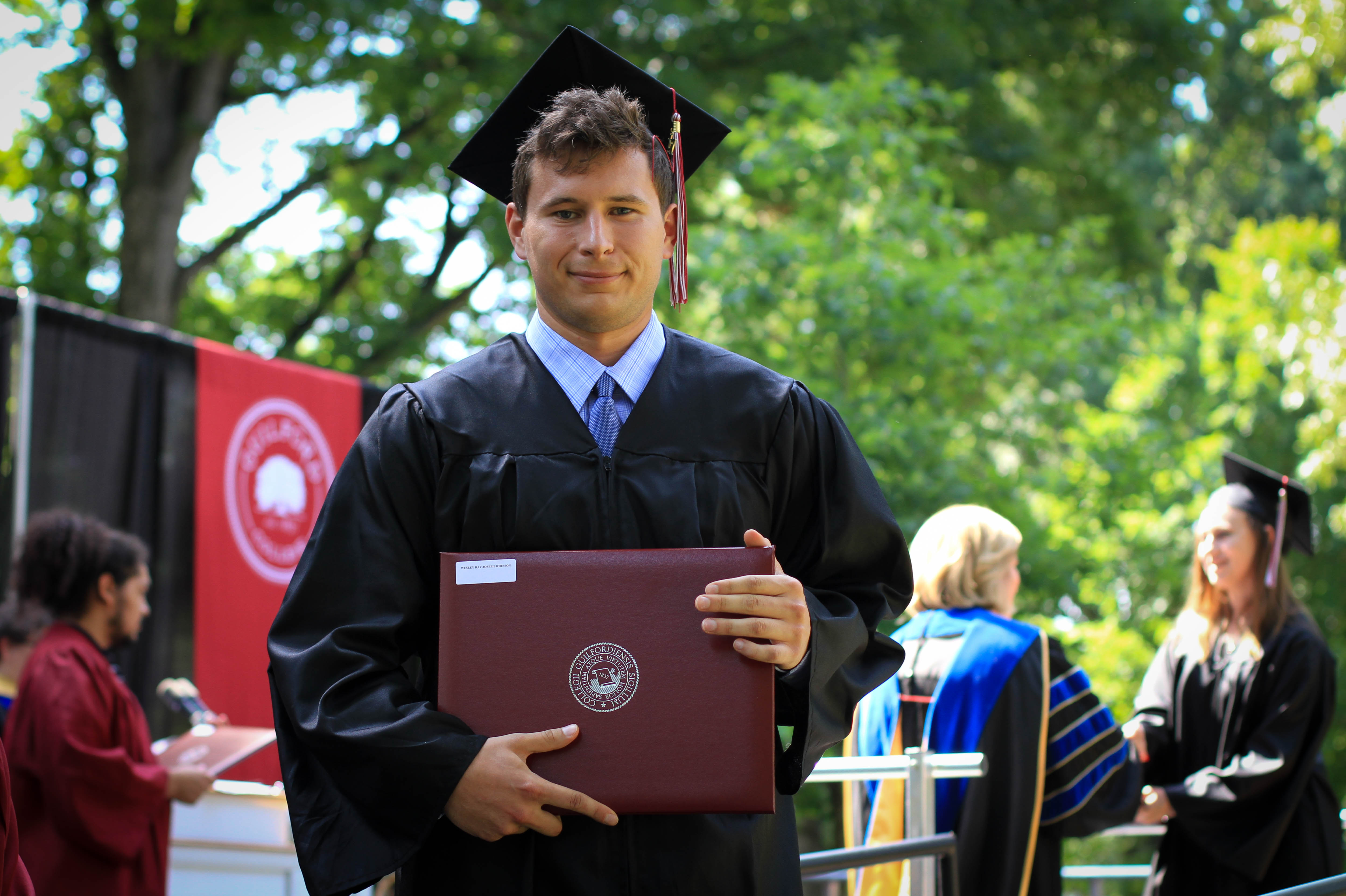 A graduate poses for the camera after receiving his diploma.