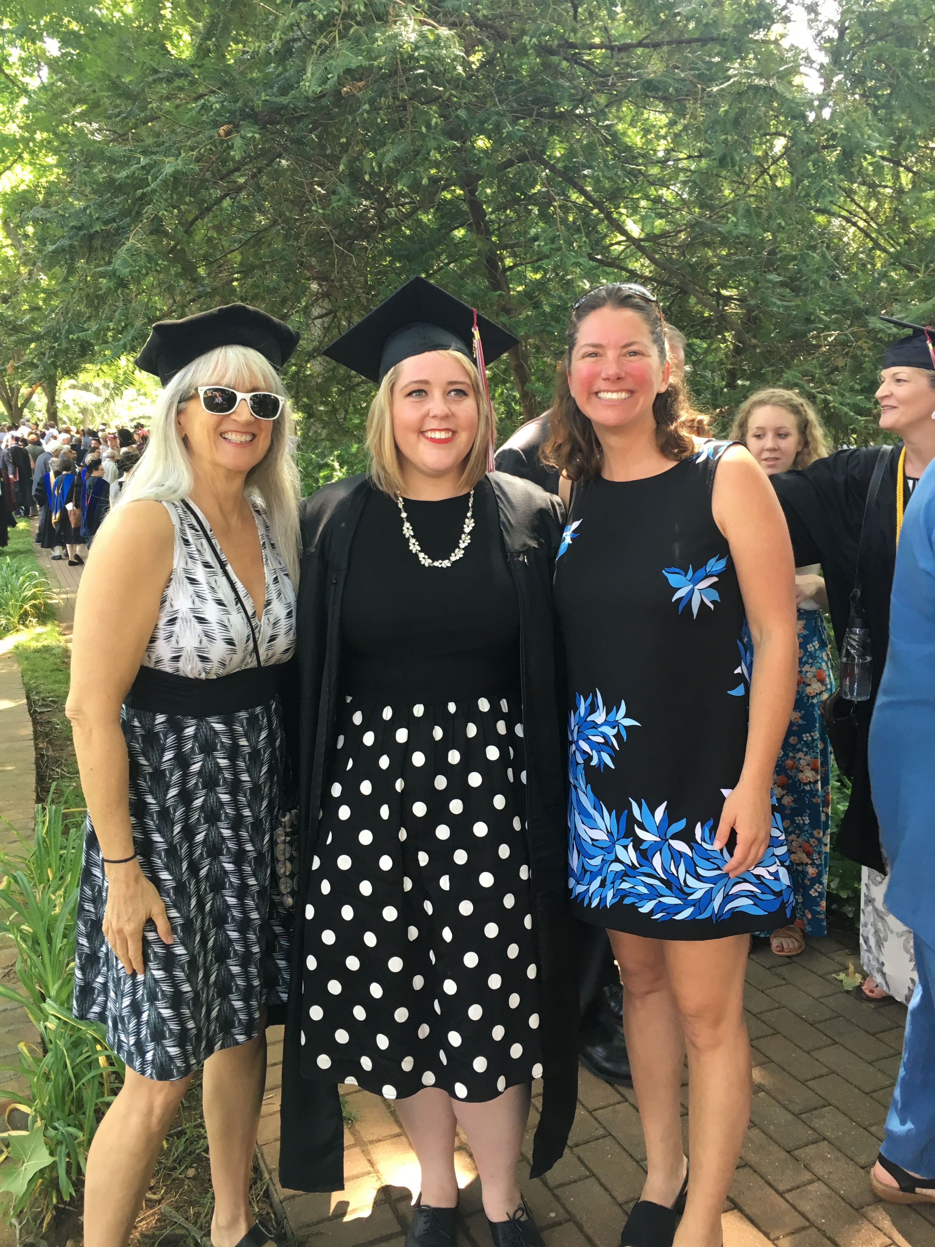 A graduate poses with Geology professors Marlene McCauley and Holly Peterson.