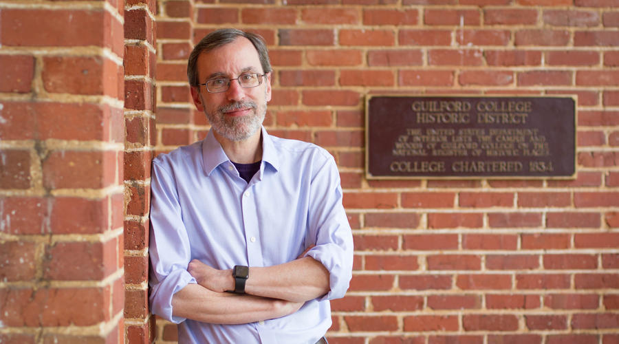 Professor Rob Whitnell poses for a photo on the porch of New Garden Hall.