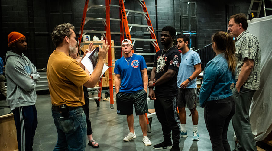A professor instructs students in the technicalities of theater lighting.