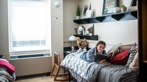 A Guilford College student reads in a room in Binford Hall.