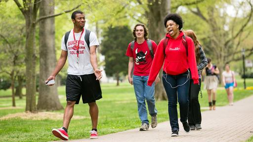 Three Guilford College students walk through the Quad.