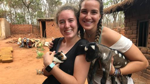 Student Mallory Cerkleski and a friend hold goats in this photo from their study abroad trip.