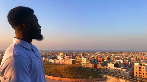 Guilford student Khassir Atchabao '20 looks over the city of Senegal in the evening.