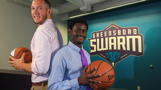 Two students pose for a photo while interning for the Greensboro Swarm basketball team.
