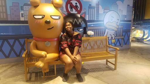 Student Mikayla Jones poses for a portrait with a large golden bear in Seoul, South Korea.