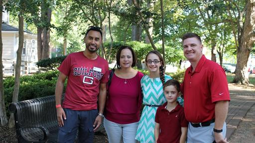 A family takes a photo wearing Guilford red at Homecoming.